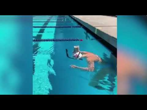 Swimmer swims with a glass of chocolate milk balanced on her head