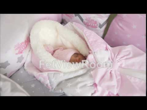 Sweet baby girl in winter overalls sleeping in the crib for a transparent canopy bed