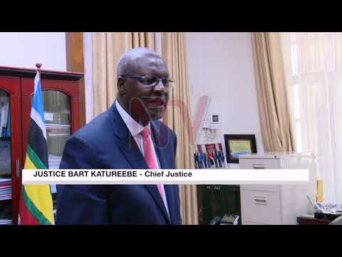 Chief Justice Bart Katureebe receives a book on genocide-related crimes