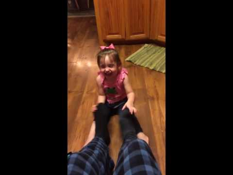 Funny little girl laughing hysterically at Daddy's feet