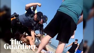 US police officer violently arrests woman on beach