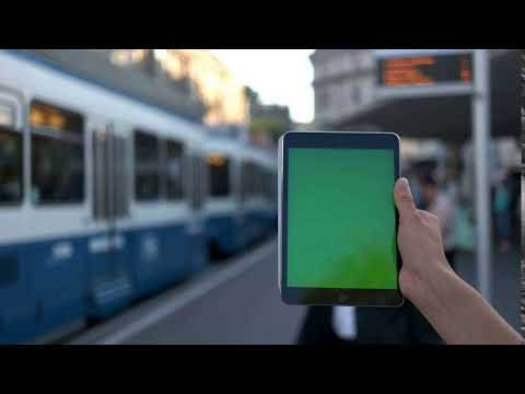 close up of mans hand holding talet with green screen at train station chroma