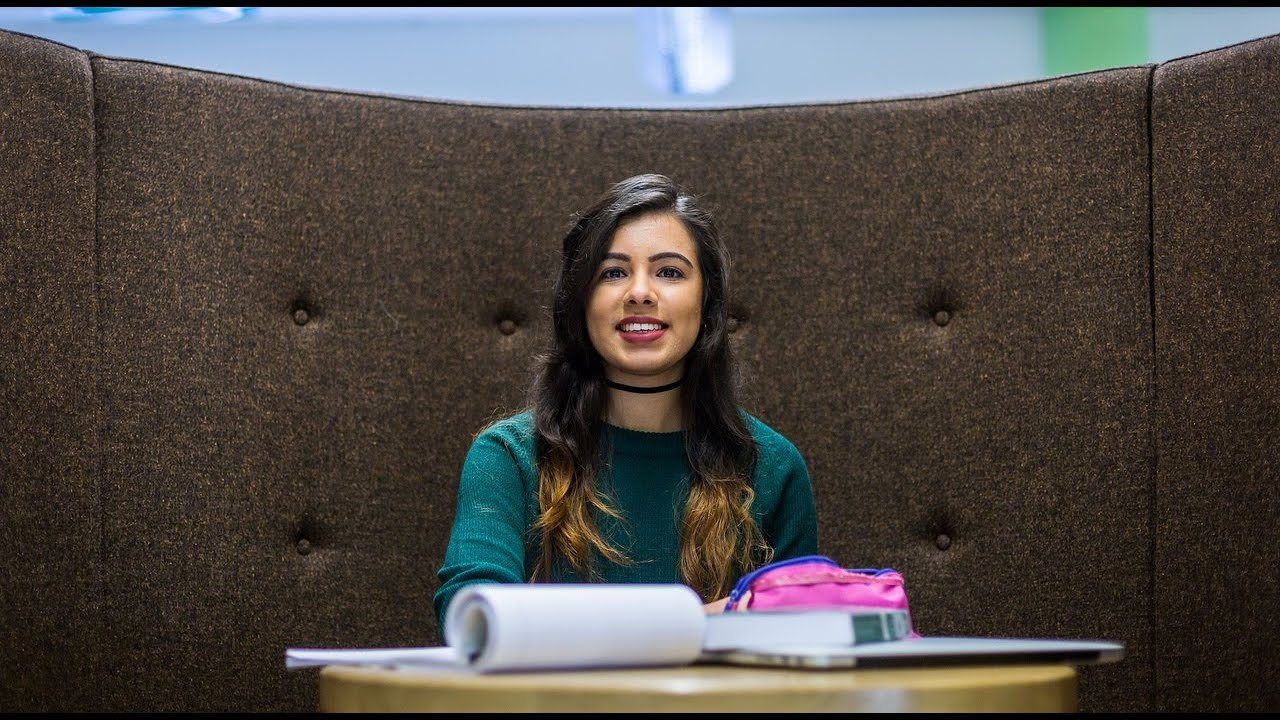 Student sitting in a study booth in front of a table which has papers and books on