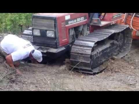 Trattore a cingoli slitta con carro di legna dal bosco.Trattori al lavoro scava buca nel terreno