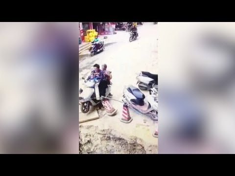 Man drives motorcycle carrying family into sinkhole