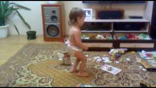 Маленькая девочка смешно танцует под музыку