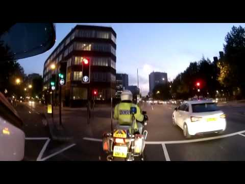 Woman jumps red light while next to Police bike
