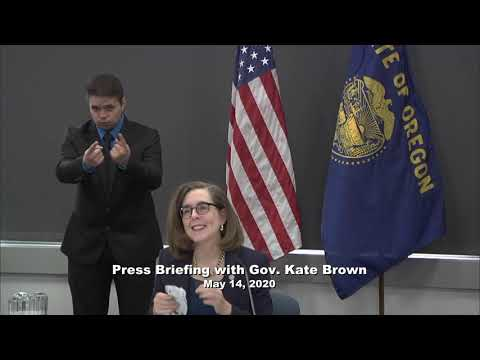 Governor Kate Brown presenting at the May 14th press conference with a sign language interpretor in the background