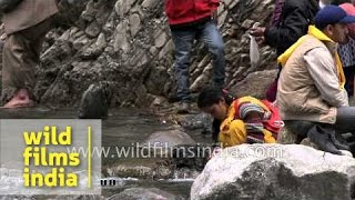 Woman carries out ablutions below slow motion Himalayan waterfall