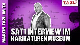 SAT1 (2019): Martin Tazl bei der Karikaturen-Ausstellung in Bonn