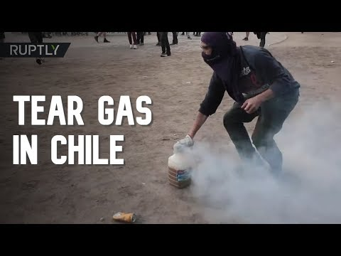 Protesters collect tear gas canisters in water jugs during clashes with police in Chile