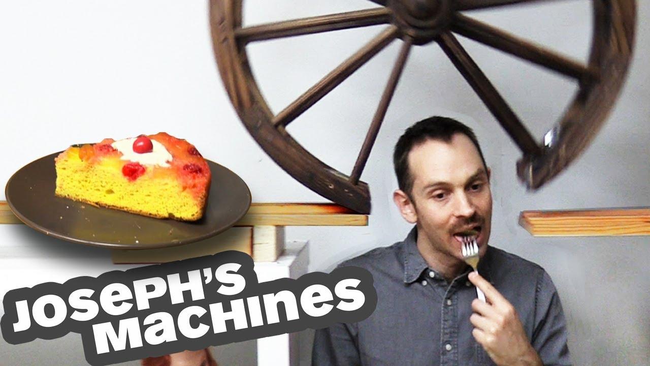 Una máquina de Rube Goldberg para cortar un trozo de tarta, compleja, precisa y altamente original