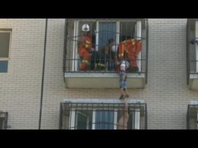 انقاذ طفل صيني عالق بسور حديد شرفة الطابق السادس