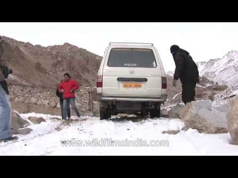 Men fix chains to car tyres for safe driving on icy roads - Ladakh
