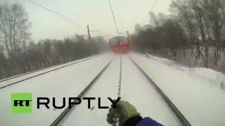 Смотреть онлайн Молодые парни прицепились к поезду и катаются на лыжах