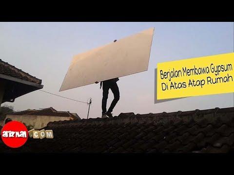 orang-berjalan-di-atas-atap-rumah-membawa-gypsum