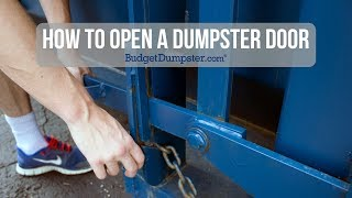 hands opening the latch of a roll off dumpster