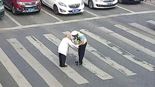 Cars waiting for the elderly to cross the street in SW China