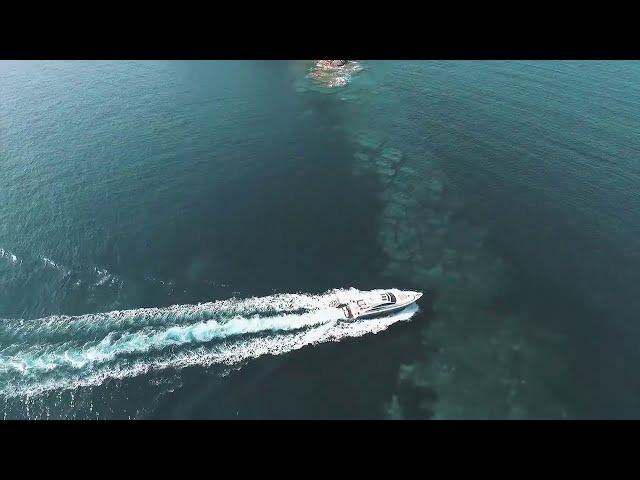 Aerial view of a luxury yacht on bright blue waters