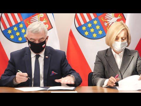 Od lewej: mężczyzna w ciemnym garniturze i maseczce na twarzy oraz kobieta w szarej marynarce i maseczce na twarzy podpisują dokumenty. W tle flagi z herbem województwa świętokrzyskiego.
