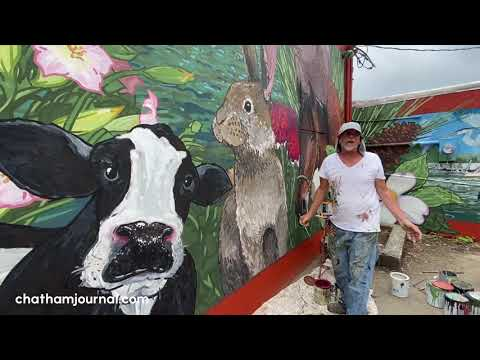 Michael Brown continues painting a mural on side of new Welcome Center