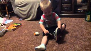 baby putting on his own shoes