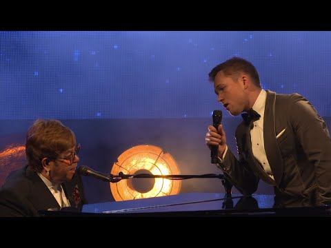 """Elton John and Bernie Taupin reflect on how emotional they felt watching biopic """"Rocketman,"""" as Elton and the film's star - Taron Egerton - duet on the title track. (May 17)"""
