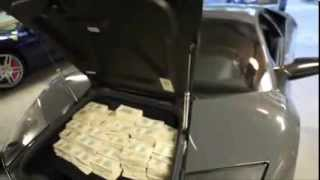 50 Cent puts money in a Lamborghini luggage carrier
