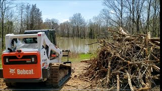 Bobcat T650 Root grapple skid steer clearing firewood and brush Illinois