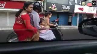 Five-year-old girl drives scooter down busy Indian road with her parents and sister riding pillion