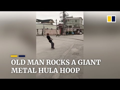 Old man works out with giant metal hula hoop
