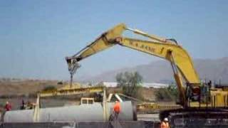 Komatsu PC1250 lowering massive section of pipe