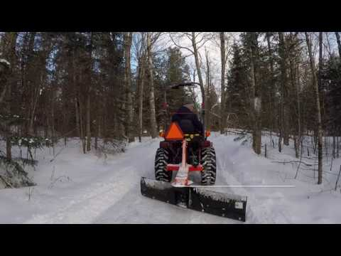 #124 Kubota B2601 Compact Tractor SnowBlower and Rear Blade Plowing Snow. outdoor channel.