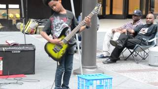 Black kid playing heavy metal music on guitar in New York