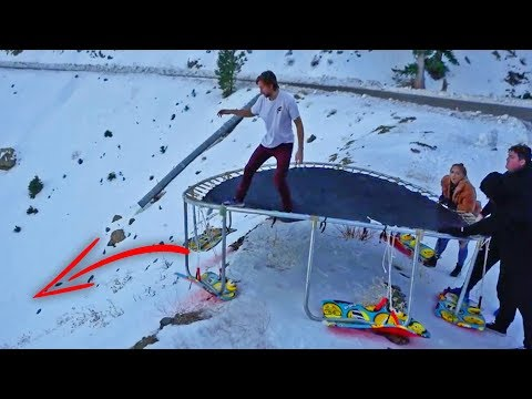 Snowboarding 15ft Trampoline Down HUGE Hill! (flips)