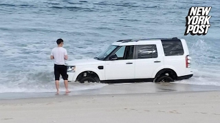 Beached SUV is nearly swept out to sea | New York Post