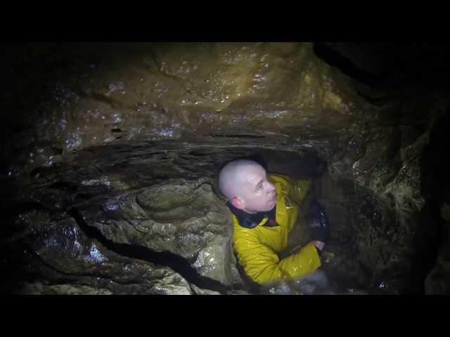 مستكشف كهوف يعلق داخل تجويف صخري تغمره المياه