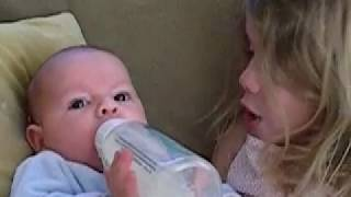 Cute Big Sister Feeding Baby Brother