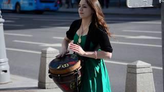 Sexy girl on Tverskaya street in Moscow, playing djembe