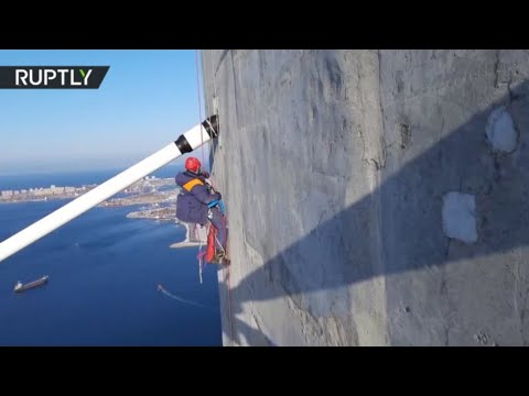 Daring alpinist cleans 320m-high Russky Bridge after freak storm glazes it with ice