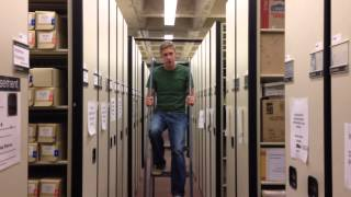 A student standing sitting on a step ladder between two rows of bookshelves.