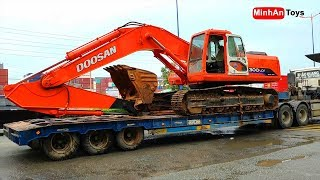 Excavator Truck: Excavator climbing on Truck, Fuso Self Loader Truck Unloading Excavator