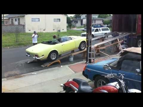 Neighbors try to build a car ramp out of boards, paint cans, and random metal.