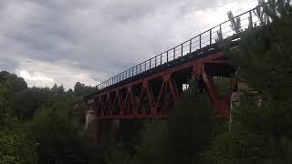Тепловоз М62 везет электричку через стариный мост