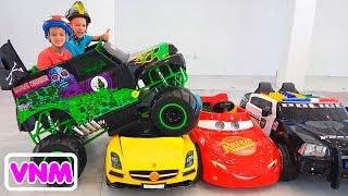 Vlad và Nikita cưỡi trên chiếc xe tải đồ chơi quái vật và đi qua những chiếc xe cho trẻ em