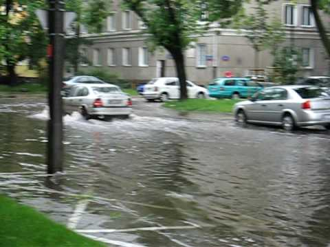 Cars Driving Through Water On The Street In Warsaw Poland