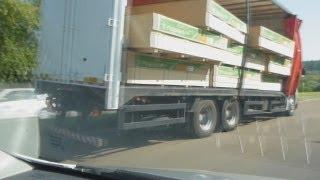 Caminhão Sider com MDF caindo a carga.
