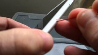 Open iPhone SIM tray with a paperclip
