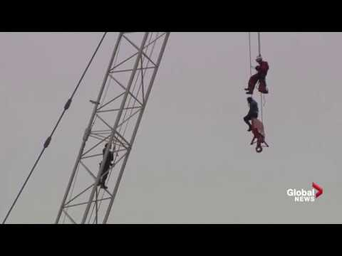 Woman stuck on crane in Toronto rescued by firefighter
