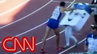 A runner celebrates by shoving 14 year old mascot